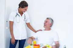 Kvinnlig doktor som talar till den höga mannen, medan ha frukosten royaltyfri fotografi