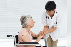 Kvinnlig doktor som talar till en hög patient i rullstol arkivfoton