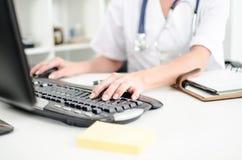 Kvinnlig doktor som tejpar på ett datortangentbord Royaltyfria Foton