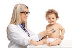 Kvinnlig doktor som undersöker en behandla som ett barnpojke royaltyfri bild