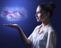 Kvinnlig doktor som visar den lilla galaxen på hennes hand arkivbild