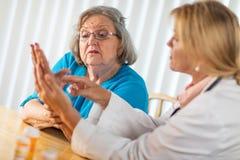 Kvinnlig doktor Talking med den h?ga vuxna kvinnan om handterapi fotografering för bildbyråer