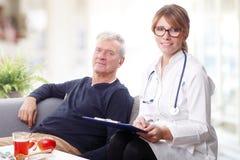 Kvinnlig doktors- och pensionärpatient Arkivbild