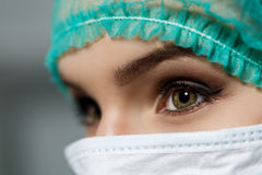 Kvinnlig doktorsframsida som bär kirurglocket för skyddande maskering och gräsplan royaltyfri fotografi