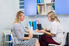Kvinnlig doktorsgynekolog med patienten på hennes kontor royaltyfri foto