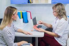 Kvinnlig doktorsgynekolog med patienten på hennes kontor arkivfoto
