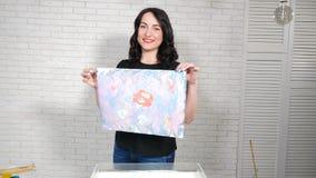 Kvinnlig ebrukonstnär som visar den färdiga konstbilden på papper Le den unga kvinnan i ljus studio Process av att skriva ut arkivfilmer
