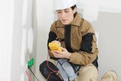 Kvinnlig elektriker som installerar den elektriska håligheten på väggen royaltyfri foto