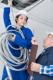 Kvinnlig elektriker som installerar ventilation i tak royaltyfri fotografi