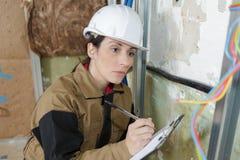 Kvinnlig elektriker som kontrollerar elektricitetsproblem fotografering för bildbyråer