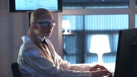 Kvinnlig elektroniktekniker som arbetar på datoren och skriver resultaten av forskningen i laboratorium arkivfilmer