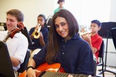 Kvinnlig elev som spelar gitarren i högstadiumorkester Arkivfoton