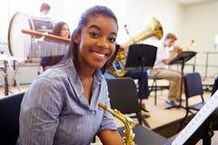 Kvinnlig elev som spelar saxofonen i högstadiumorkester Arkivbilder