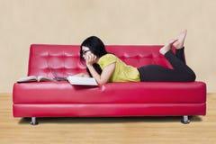 Kvinnlig elev som studerar, medan ligga på soffan Royaltyfria Foton