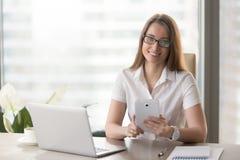 Kvinnlig entreprenör som i regeringsställning använder den digitala minnestavlan royaltyfri bild