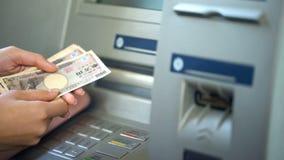 Kvinnlig fående japansk yen från maskinen för automatisk kassör, återta för kassa royaltyfri foto