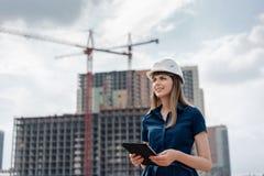 kvinnlig för konstruktionstekniker Arkitekt med en minnestavladator på en konstruktionsplats Se för ung kvinna som bygger arkivbilder