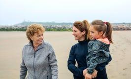 Kvinnlig för tre utvecklingar som går på stranden Fotografering för Bildbyråer