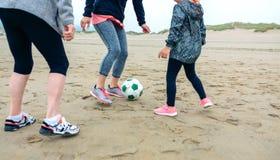Kvinnlig för tre utvecklingar som spelar fotboll på stranden Fotografering för Bildbyråer