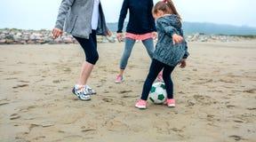 Kvinnlig för tre utvecklingar som spelar fotboll på stranden Royaltyfri Foto