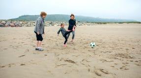 Kvinnlig för tre utvecklingar som spelar fotboll på stranden Royaltyfri Bild