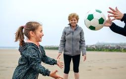 Kvinnlig för tre utvecklingar som spelar på stranden Arkivfoto