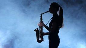 Kvinnlig för yrkesmässig musiker för kontur som spelar på saxofonen Rökig isolerad studio arkivfilmer