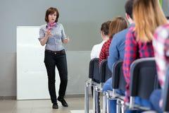 Kvinnlig föreläsare som levererar presentation till åhörare arkivbild
