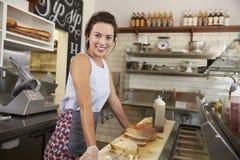 Kvinnlig företagsägare av en smörgåsstång på arbete, sidosikt Arkivfoto