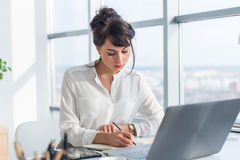 Kvinnlig författare som arbetar i det ljusa moderna kontoret som ner skriver nya idéer hennes anteckningsbok som söker informatio Royaltyfria Foton