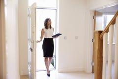 Kvinnlig fastighetsmäklare i hallet som ut bär värdering arkivfoto