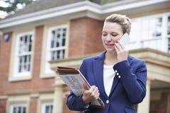 Kvinnlig fastighetsmäklare på bostads- egenskap för telefonyttersida arkivfoton