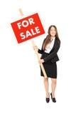 Kvinnlig fastighetsmäklare som rymmer ett till salu tecken Royaltyfri Bild