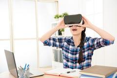 Kvinnlig flicka i skjortan som rymmer VR-apparaten Royaltyfria Bilder