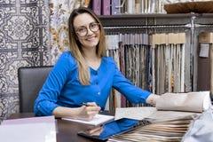 Kvinnlig formgivare f?r arbetsplats, aff?rskvinna i exponeringsglas med anteckningsbokpennan och pr?vkopia av tyg som arbetar i k arkivbild