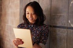 Kvinnlig formgivare In Modern Office som arbetar på den Digital minnestavlan Arkivfoto