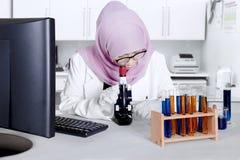 Kvinnlig forskare med mikroskopet i labbet Arkivfoto
