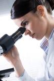 Kvinnlig forskare som använder nära övre för mikroskop Arkivfoto