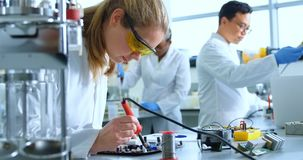 Kvinnlig forskare som löder strömkretsbrädet 4k stock video