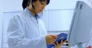 Kvinnlig forskare som ser skrivplattan 4k lager videofilmer