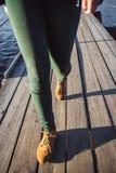 Kvinnlig fot i bruna känga- och gräsplanflåsandemoment på wood bakgrund Gå mode som fotvandrar begrepp Royaltyfria Foton