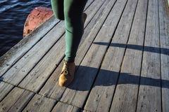 Kvinnlig fot i bruna känga- och gräsplanflåsandemoment på wood bakgrund Gå mode som fotvandrar begrepp placera text Arkivfoton