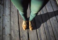 Kvinnlig fot i bruna kängor och gräsplanflåsanden som står på wood bakgrund Gå mode som fotvandrar begrepp Royaltyfria Bilder