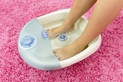 Kvinnlig fot i en vibrerande fotmassager Elektriskt massagefotbad koppla av arbete Royaltyfri Fotografi