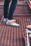 Kvinnlig fot i flåsandena och skorna på skeppsdockan Fotografering för Bildbyråer