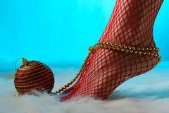 Kvinnlig fot i röda strumpor som slås in med guld- pärlor Royaltyfria Foton