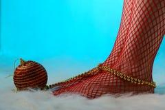 Kvinnlig fot i röda strumpor som slås in med guld- pärlor Royaltyfri Fotografi