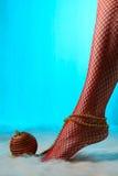 Kvinnlig fot i röda strumpor som slås in med guld- pärlor Royaltyfria Bilder