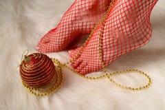 Kvinnlig fot i röda strumpor som slås in med guld- pärlor Royaltyfri Foto