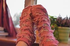 Kvinnlig fot i rosa woolen sockor vid fönstret, för korrigeringsfoto för retro stil tonalt filter Royaltyfri Bild